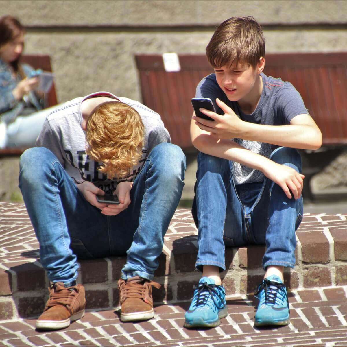 2 boy sitting on brown floor while using their smartphone 159395
